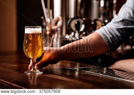 Drinks, Fun, Meeting, Oktoberfest. Barman Serves Light Beer With Foam On Wooden Bar Counter In Inter