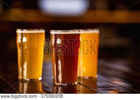 Beer Craft Style. Barley, Unfiltered, Light Drink In Glasses On Wooden Table In Blurry Interior Of P
