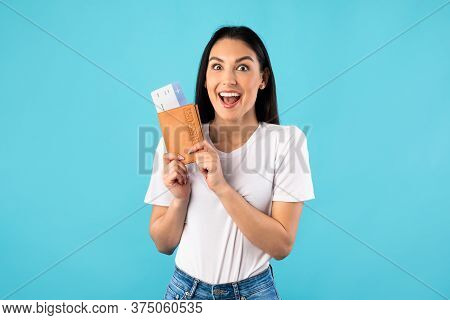Cheap Flights Concept. Overjoyed Young Woman Holding Tickets And Passport, Standing On Turquoise Stu