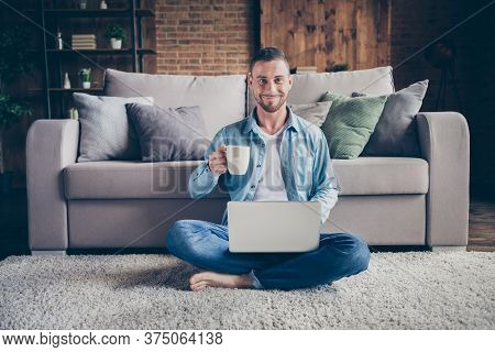 Photo Of Handsome Homey Guy Sitting Comfy Fluffy Carpet Near Couch Drink Hot Fresh Coffee Browsing N