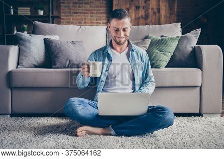 Photo Of Handsome Homey Guy Relaxing Sitting Comfy Fluffy Carpet Near Couch Drink Coffee Browsing No