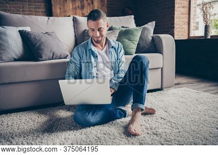 Photo Of Handsome Homey Guy Relaxing Sitting Comfy Fluffy Carpet Near Couch Browsing Notebook Freela
