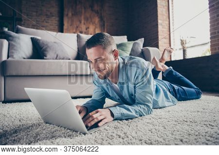 Closeup Photo Of Handsome Homey Guy Relaxing Lying Comfy Fluffy Carpet Near Couch Browsing Notebook