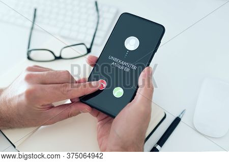 Close-up View Of Person Rejecting Call From Unknown Number With Text Unbekannter Anrufer, German For