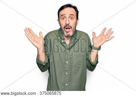 Middle age handsome man wearing casual green shirt over isolated white background clueless and confused with open arms, no idea and doubtful face.