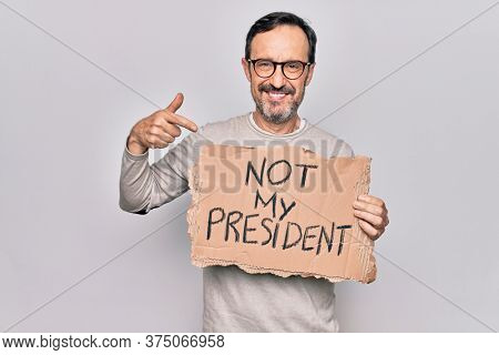 Middle age handsome man on disagreement holding banner with not my president message smiling happy pointing with hand and finger