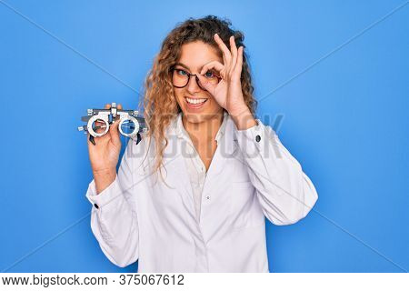 Beautiful oculist woman with blue eyes holding optometry glasses over isolated background with happy face smiling doing ok sign with hand on eye looking through fingers