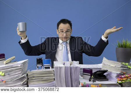Outraged Businessman Waving His Hands Over Desk Full Of Documents. The Concept Of Overload And Busin