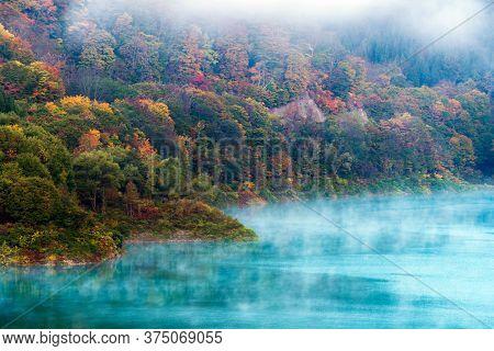 Morning Mist with Autumn Fall Lake and Forest at Tamagawa Dam in Akita Tohoku Japan