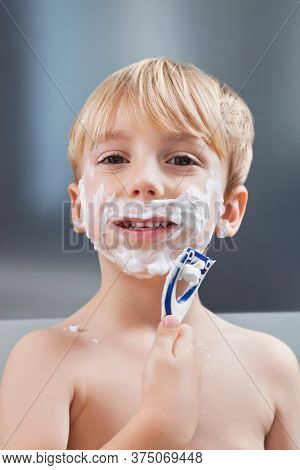 Portrait of Caucasian boy pretending to shave his face