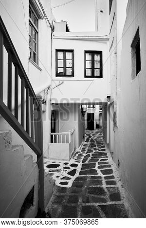 Perspective of old street in Mykonos town, Greece. Black and white architectural photography
