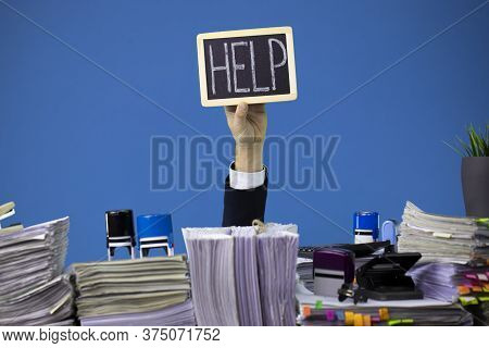 Hand Of Caucasian Businessman Emerging From Office Desk Loaded Of Paperwork, Invoices And Lot Of Pap