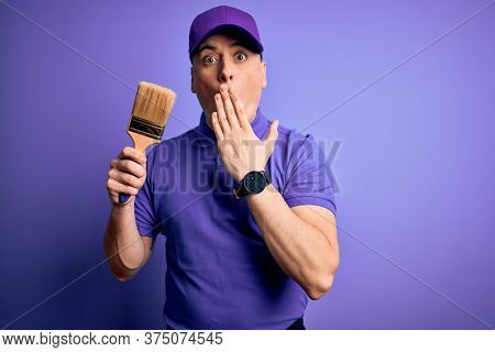 Young modern decorator painter man holding paint brush over purple background cover mouth with hand shocked with shame for mistake, expression of fear, scared in silence, secret concept