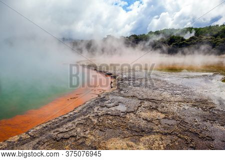 New Zealand. The unique geothermal zone of Rotorua. Orange shores of a hot lake with gas bubbles. Wai-O-Tapu. Thermal Wonderland Champagne. The concept of exotic, ecological and photo tourism