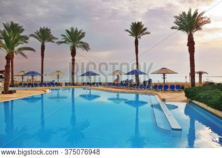 DEAD SEA, ISRAEL - DECEMBER 30, 2011: Winter in the Dead Sea. The picturesque swimming pool, palm trees and beach umbrellas