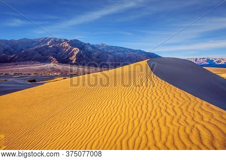 USA. The sand lies in light waves. The dunes are located along Road 190. Magical desert morning. Mesquite Flat Sand Dunes - dunes in Death Valley. The concept of active and photo tourism