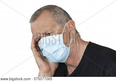 Man With Medical Protection Mask Sitting Holding His Head In His Hand While Thinking Or Contemplatin