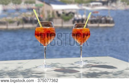 Close Up Of Two Glasses Of Chilled Cocktail Drinks With Straws And  Ice Cubes On A Table Near The Be