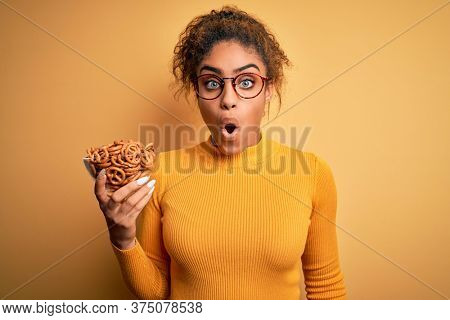 African american afro girl holding bowl with german baked pretzels over yellow background scared in shock with a surprise face, afraid and excited with fear expression