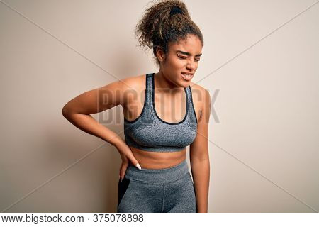 Young african american sportswoman doing sport wearing sportswear over white background Suffering of backache, touching back with hand, muscular pain