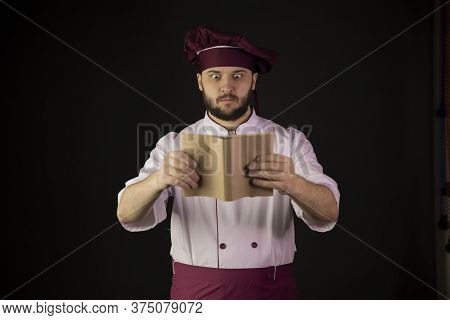 Surprised Handsome Chef Man In Uniform Holds Cookbook. Cook In Apron Looking On Recipe-book On Black