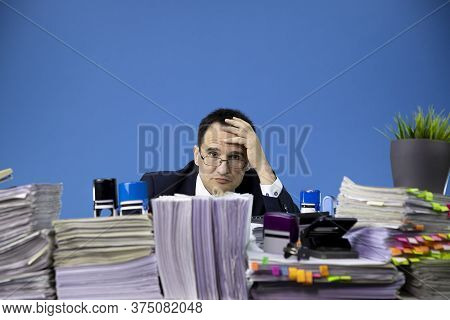 Exhausted Tired Middle-aged Overworked Businessman Wearing Glasses Looks Out Of Huge Stack Of Docume