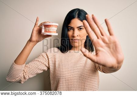 Young beautiful hispanic dentist woman holding prosthesis dental mouth with open hand doing stop sign with serious and confident expression, defense gesture