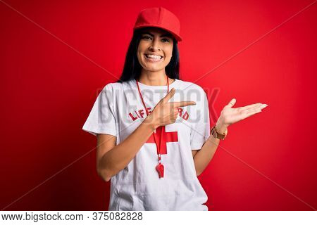 Young beautiful hispanic lifeguard woman wearing safeguard t-shirt and whistle amazed and smiling to the camera while presenting with hand and pointing with finger.