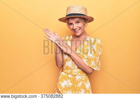 Beautiful blonde woman on vacation wearing summer hat and dress over yellow background clapping and applauding happy and joyful, smiling proud hands together