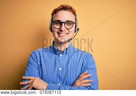 Young handsome redhead call center agent man wearing glasses working using headset happy face smiling with crossed arms looking at the camera. Positive person.