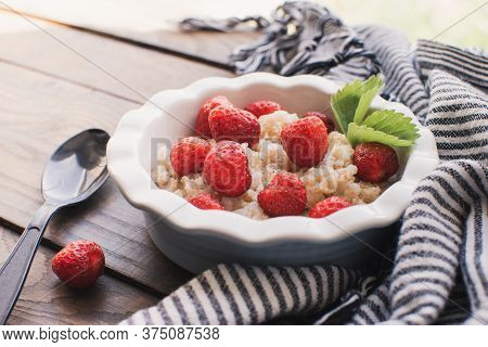 Breakfast. Tasty oatmeal with berries. Healthy breakfast ingredients. Oat granola in bowl with strawberry and mint. Granola for breakfast with berries.