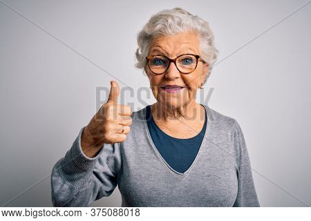 Senior beautiful grey-haired woman wearing casual sweater and glasses over white background doing happy thumbs up gesture with hand. Approving expression looking at the camera showing success.