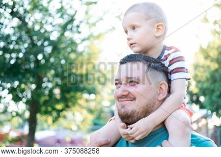 Funny Blond Boy With His Father Are In The Park. Boy Is Sitting On The Fathers Shoulders. Happy Adul