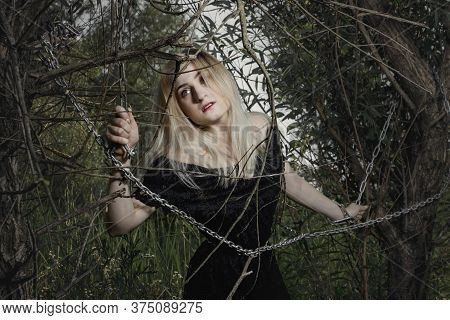 The Girl Is Chained To A Tree. Girl In A Black Dress With Chained Hands In The Forest