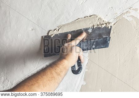 Hand With Putty Knife Repair Wall, Hand With A Spatula, Spatula With Spackle Paste Structure, Proces