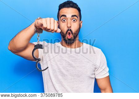 Young hispanic man holding prisoner handcuffs scared and amazed with open mouth for surprise, disbelief face