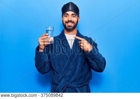 Young hispanic man wearing sleep mask and robe drinking water smiling happy pointing with hand and finger
