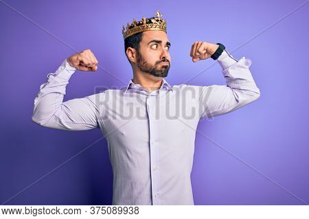 Young handsome man with beard wearing golden crown of king over purple background showing arms muscles smiling proud. Fitness concept.