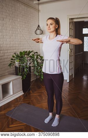 Young Woman Practicing Pilates And Yoga Exercises At Home.