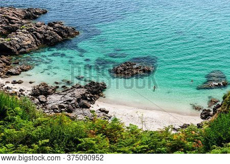 Hidden Cove In Finisterre On A Late Summer Afternoon In Galicia, Spain, With Incidental Bathers In T