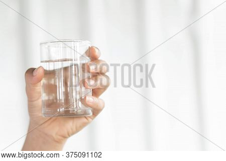 Closeup Woman Hand Holding A Glass Of Pure Water For Dink With Grey Background, Health Care Concept