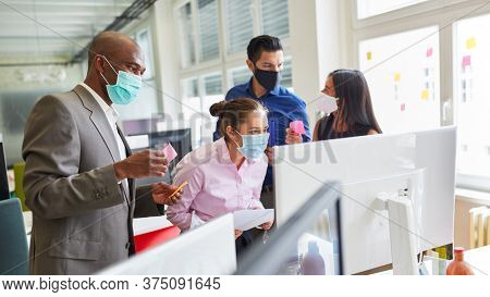 Creative start-up business team of an internet agency with face mask because of Covid-19 on the computer