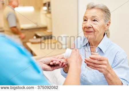 Caregiver gives senior woman as patient tablets in supervised senior citizen apartment