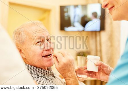Senior as a patient takes his tablets in assisted living or nursing home