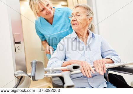 Senior in a wheelchair at the nursing home and caring nurse