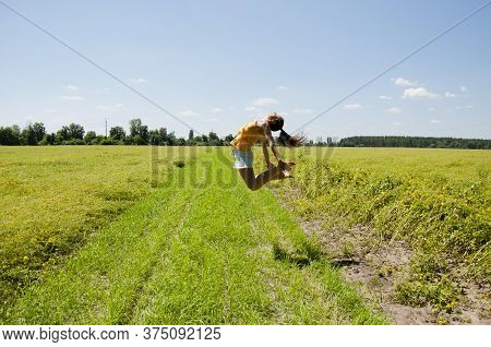 Free Girl Jump High. Absorb Solar Energy. Closer To Sun. Woman Jumping In Field. Female Fly Above Gr
