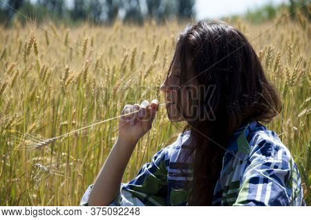 Girl Resting In Village Near Hay. Young Girl On Ranch. Woman Beautiful Long Hair Nature Background.