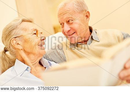 Happy retired senior couple together reading a book in retirement home