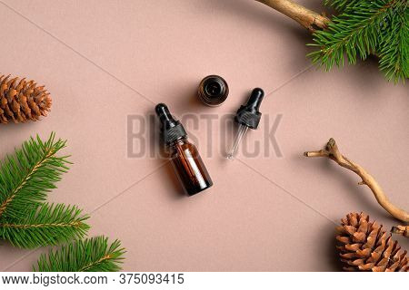 Flat Lay Composition With Bottles Of Conifer Essential Oil On Beige Background. Natural Organic Cosm
