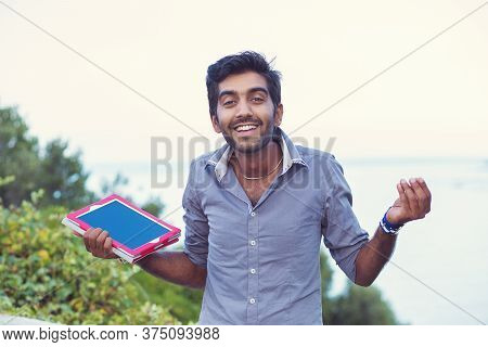 Confused Student. Closeup Portrait Puzzled Clueless Young Man Holding, Showing Tablet Pad Screen, Ar